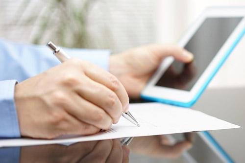 man writing on from with tablet